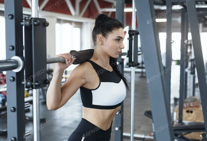 Bodybuilding workout. Young woman using exercise machine in gym
