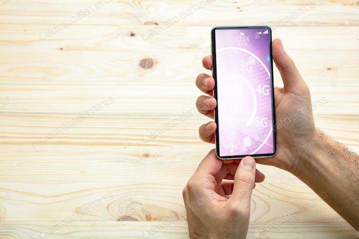 Mann hält ein Smartphone, Internet-Geschwindigkeitstest auf dem Bildschirm, Holzhintergrund, Kopierraum