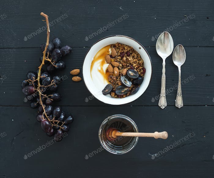 Healthy breakfast set. Bowls of oat granola with yogurt, fresh grapes, almond and honey