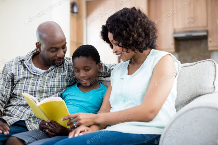 Parents reading book with their son in living room