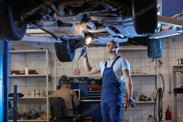 Muscular Mechanic Inspecting Car on Lift