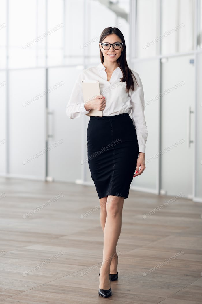 Smiling businesswoman walking along the office corridor with a tablet computer
