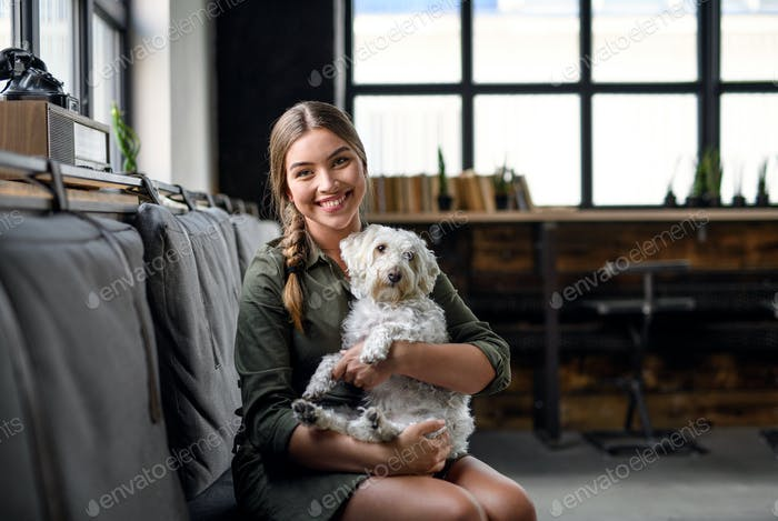 Portrait of young business woman with dog indoors in office, looking at camera