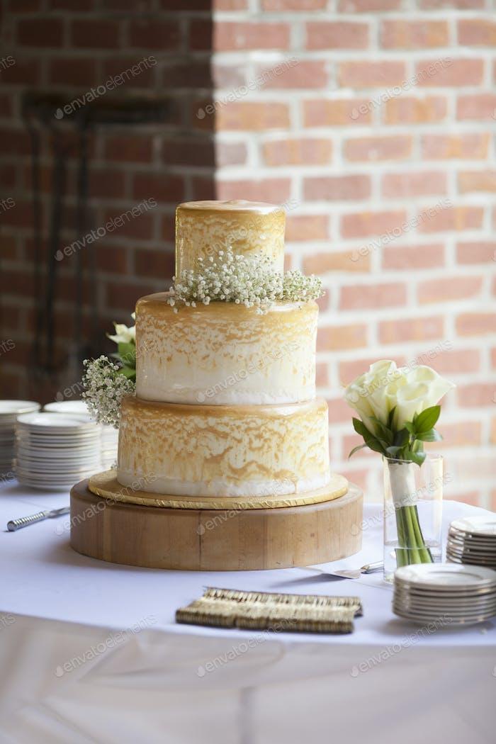 Three tiered wedding cake at outdoor reception