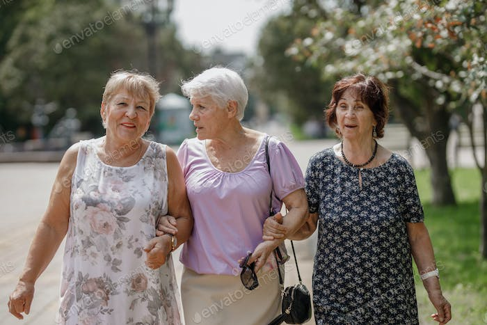 Three old women walking together in the park on a warm day