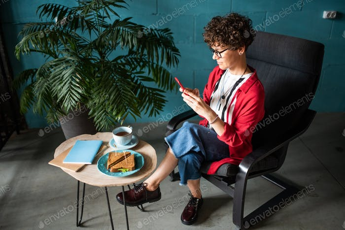 Young female in elegant casualwear photographing snack and drink on table