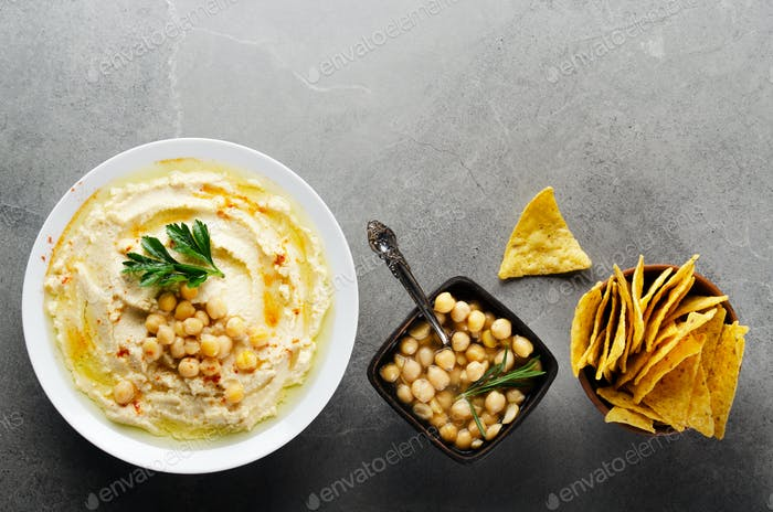 Flat lay Hummus in clay dish topped with chickpeas and green coriander leave
