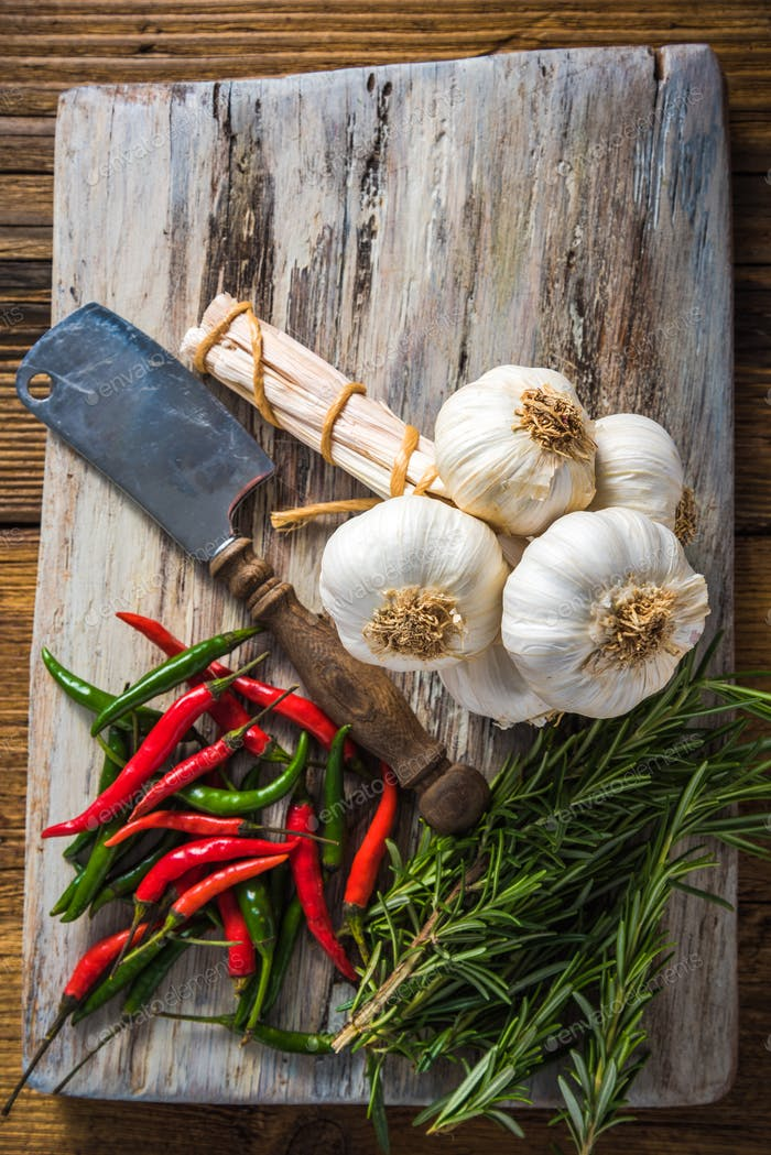 Fresh whole garlic and spices on chopping board