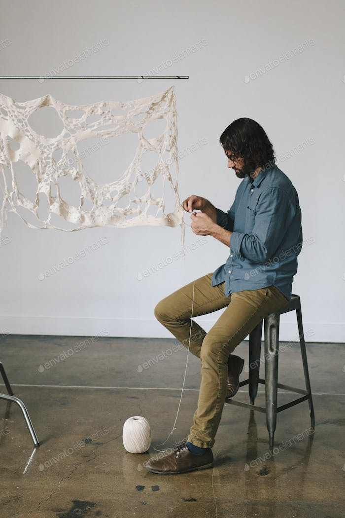 An artist working on an art piece, creating a woven and stitched object with thread.