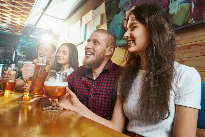 Friends laughing and joking while drinking ale in pub