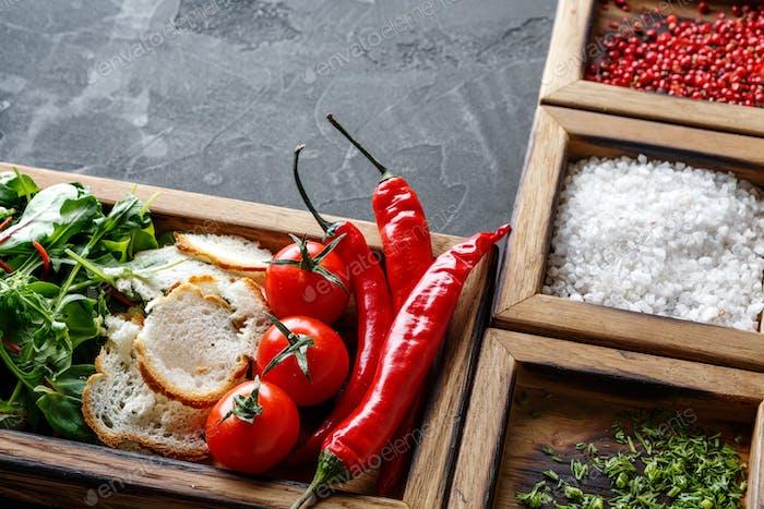 Zutaten und Kräuter in Holzkiste auf dunklem Hintergrund kochen