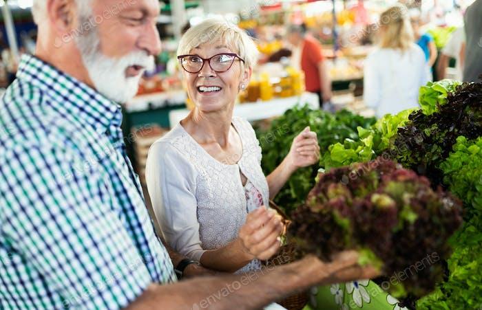 Pareja madura comprando verduras y frutas en el mercado. Dieta saludable