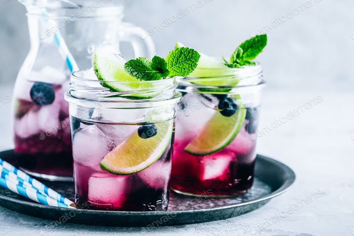 Blueberry Mojito with lime and fresh mint. Iced cold summer drink in glass jar.