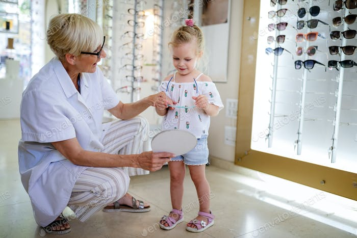 Thumbnail for Child at eye sight test. Little kid selecting glasses at optician store