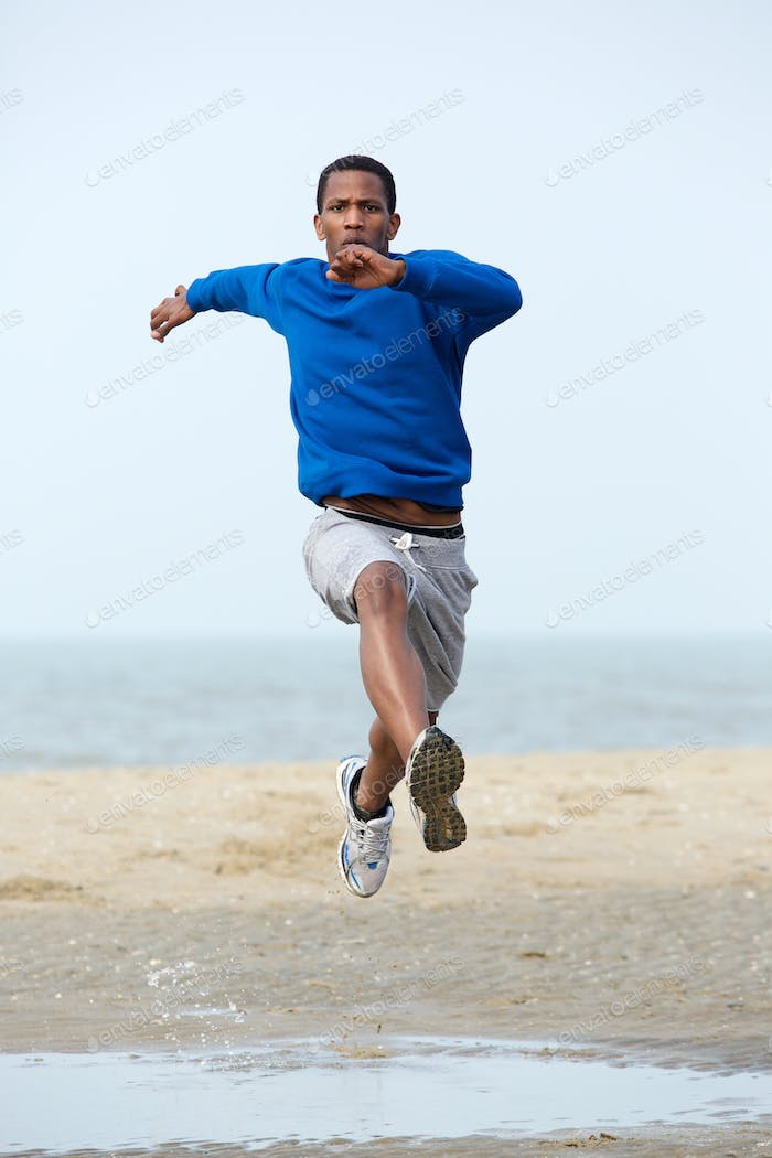 Young male athlete running at the beach.