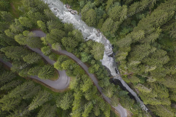 aerial view of a waterfall and a mountain road winding through a fir forest