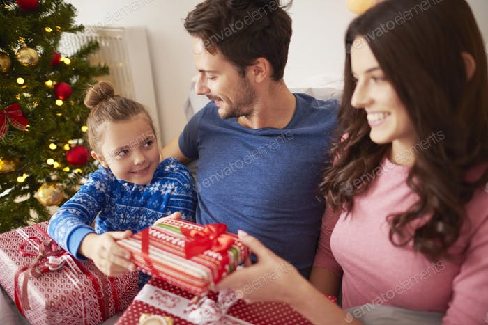 Family sharing the Christmas presents in the bed