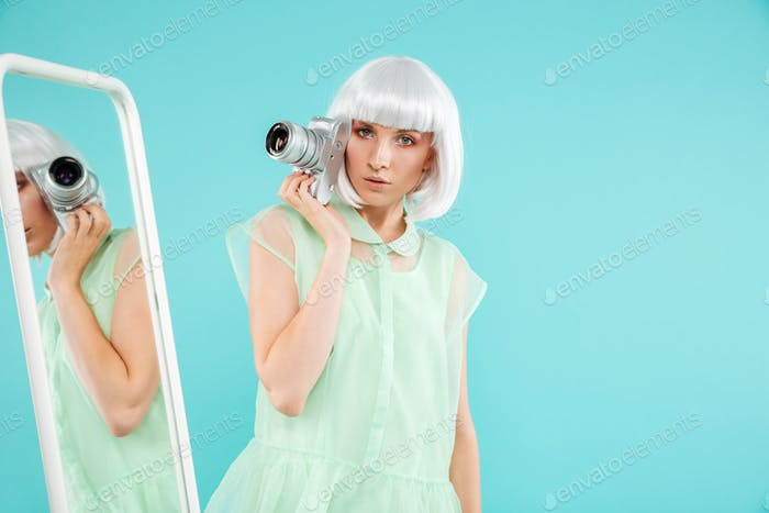 Stylish young woman photographer with photo camera near the mirror