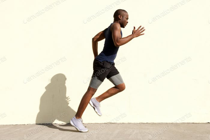 Full body profile of healthy young black man running by wall
