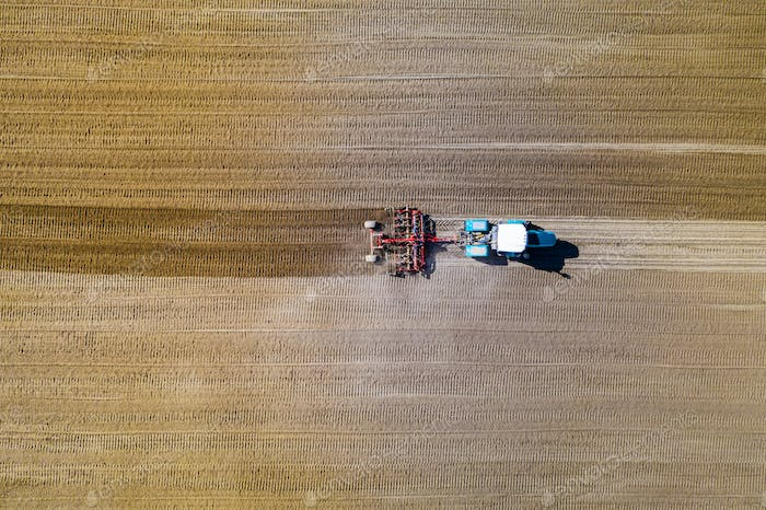 Aerial view of tractor with mounted seeder on plowed agricultural field