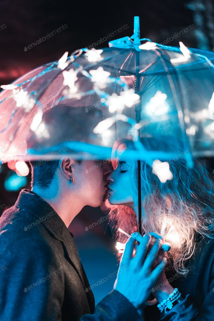 Thumbnail for Guy and girl kissing under an umbrella