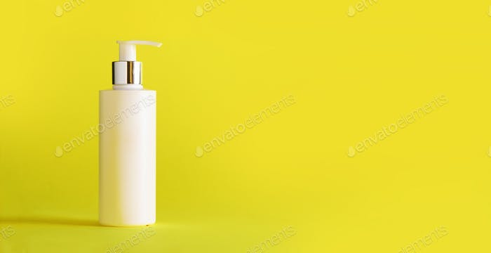 White bottle of moisturizing lotion on yellow background with copy space. Minimalism style. Skin