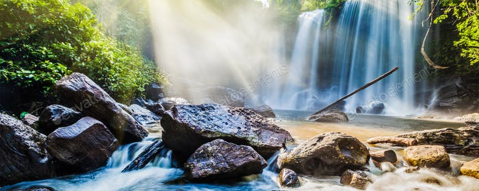 Tropical waterfall in jungle with sun rays