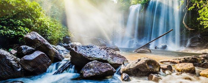 Cascada tropical en selva con rayos de sol