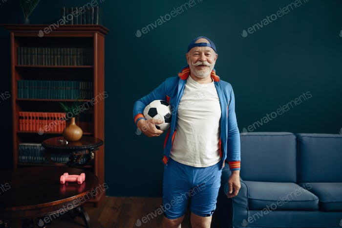 Elderly sportsman in uniform poses with ball