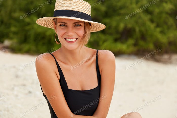 Portrait of glad female in beach hat and bathing suit, has bare shoulders, healthy tanned skin, enjo