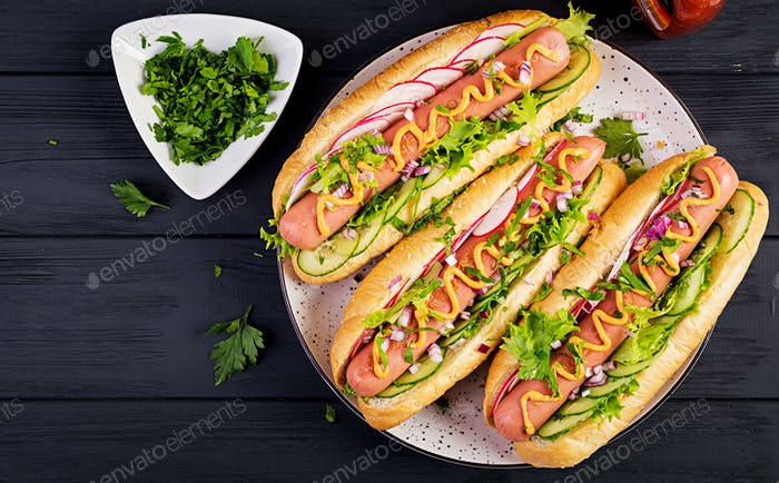 Hot dog with  sausage, cucumber, radish and lettuce on dark wooden background.