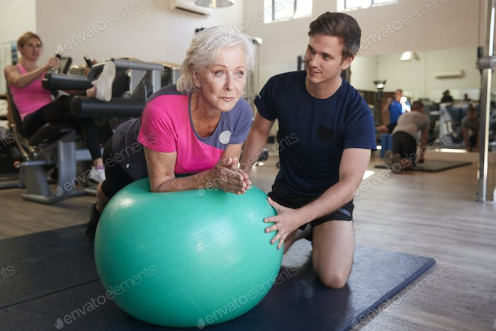 Senior Woman Exercising On Swiss Ball Being Encouraged By Personal Trainer In Gym