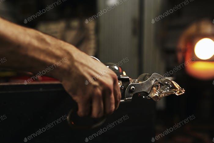 Ein Glasbläser hält ein mundgeblasenes Glasobjekt und schneidet es von dem Metallrohr ab, das verwendet wird, um die