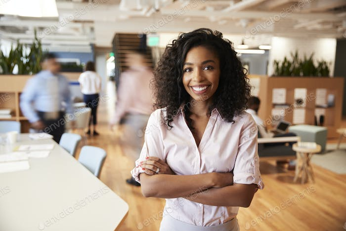 Portrait Of Businesswoman In Busy Modern Office With Blurred Colleagues Working In Background