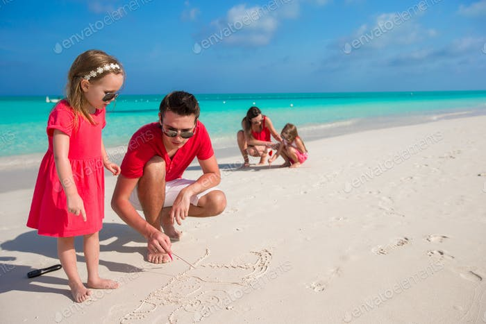 Young family painting on the sand during vacation