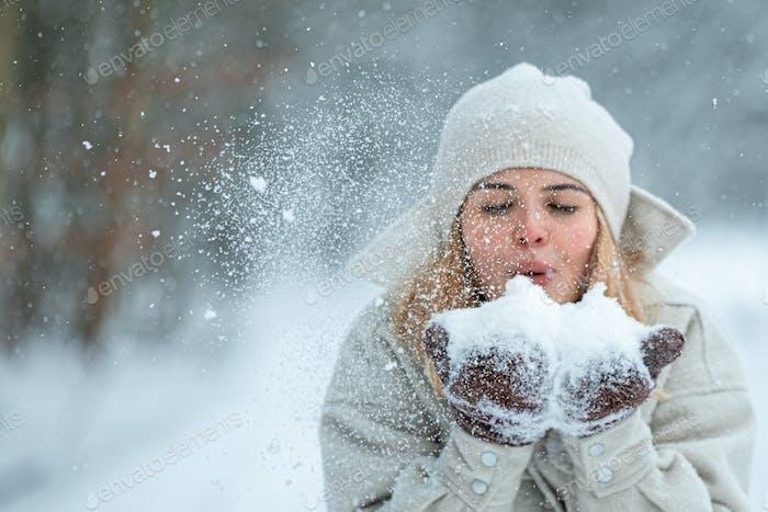 Chica feliz jugando con nieve al aire libre