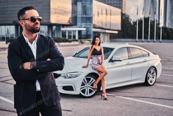 Хорошо одетая привлекательная пара, опираясь на роскошный автомобиль на открытом воздухе против небоскреба.