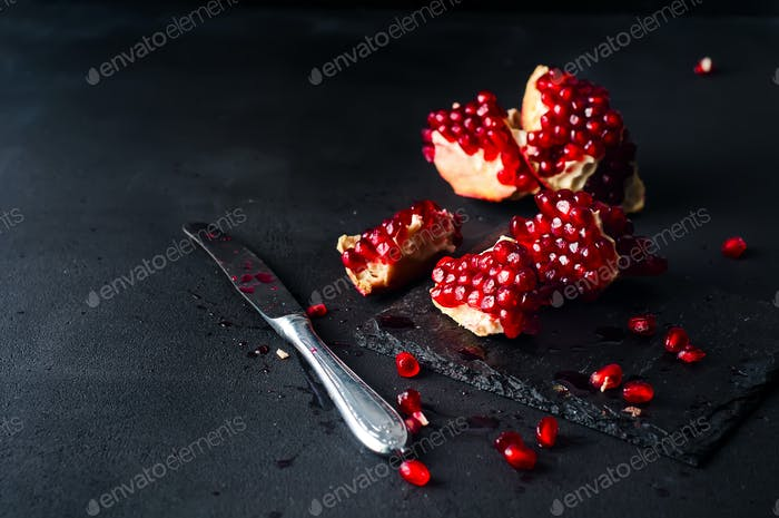 Pomegranates and pomegranate seeds on a dark background