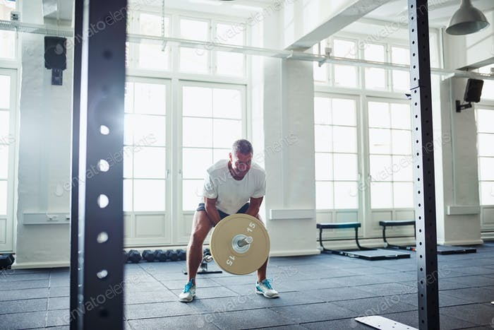 Senior Mann angespannt beim Heben von Gewichten in einem Fitnessstudio