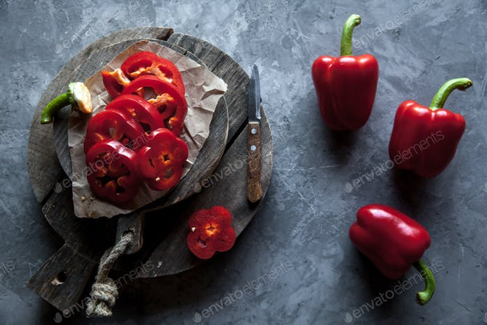Sliced sweet pepper on a cutting Board with a knife and ripe pepper