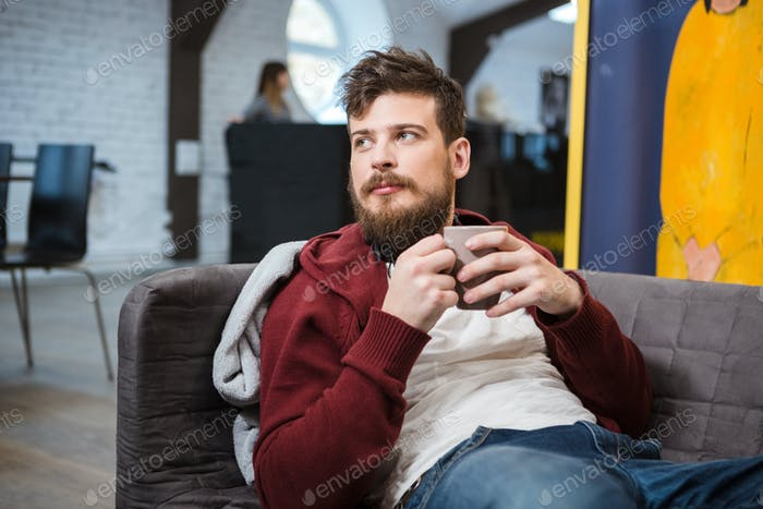 Handsome young man lying on sofa with cup of tea