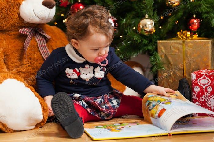 Toddler baby girl reading fairy tales near christmas tree.