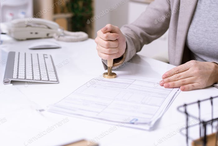 Hands of young female office worker putting seal on financial document