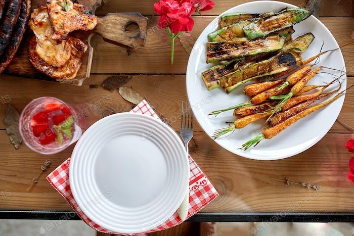 Esstisch mit Fleischgrill, gebratenem Gemüse, Saucen und Limonade, Abwechslung