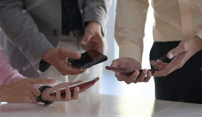 Many employees hold their smartphones near each other to exchange wireless data.
