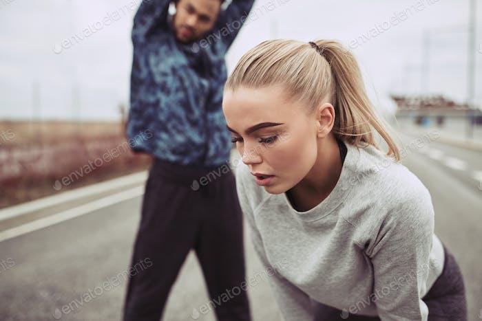 Молодая пара в спортивной одежде готовится к дороге бежать вместе