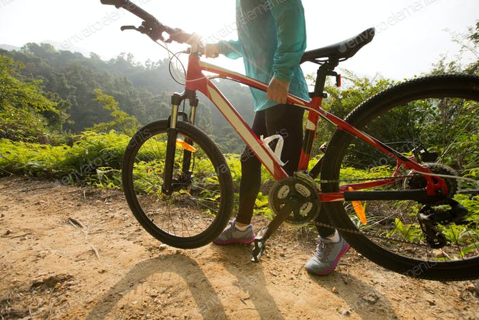 Woman with mountain bike on forest trail