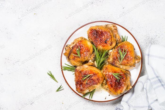 Gebackene Hähnchenschenkel mit Kräutern auf weißem Teller
