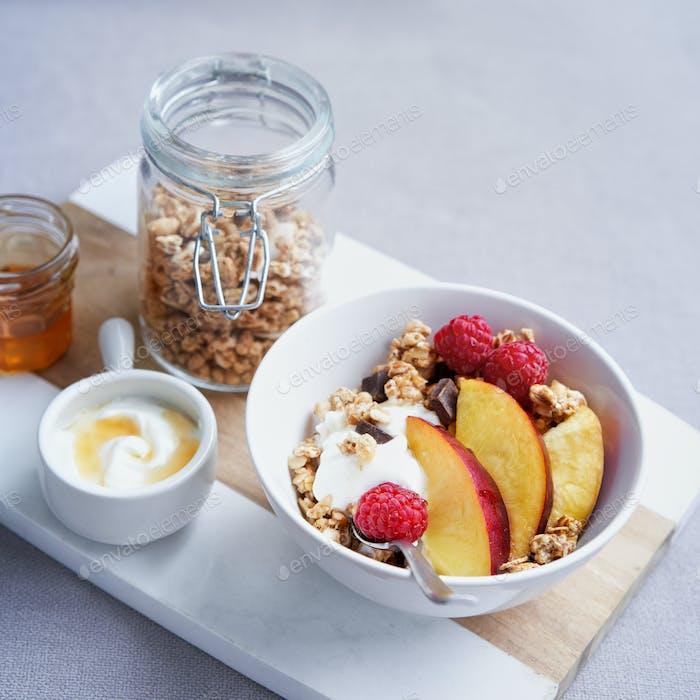 Bowl of homemade granola with yogurt, honey, fresh raspberries and nectarines