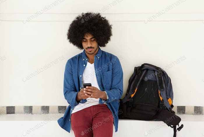 Cool travel guy sitting with mobile phone and bag